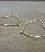 Gold hoop earrings with an organic design